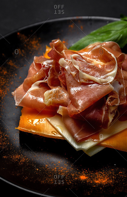 Homemade toasted bread with ham and different types of cheeses on dark background
