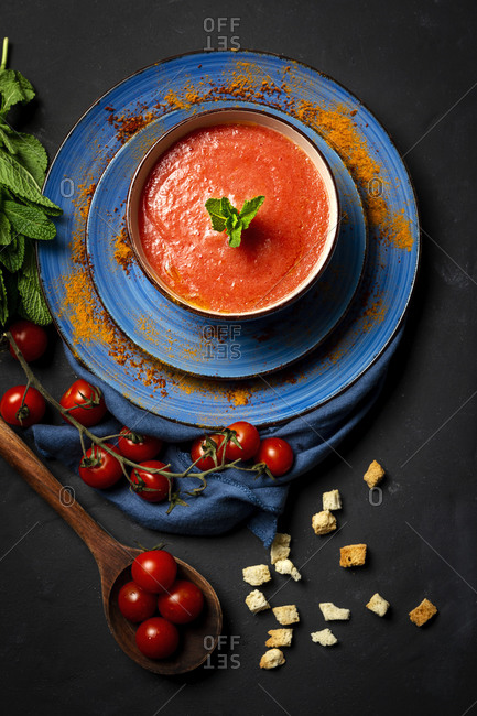 Healthy Homemade Tomato Soup with Bread, Mint and Olive Oil on Dark Background from above. Vegan food concept