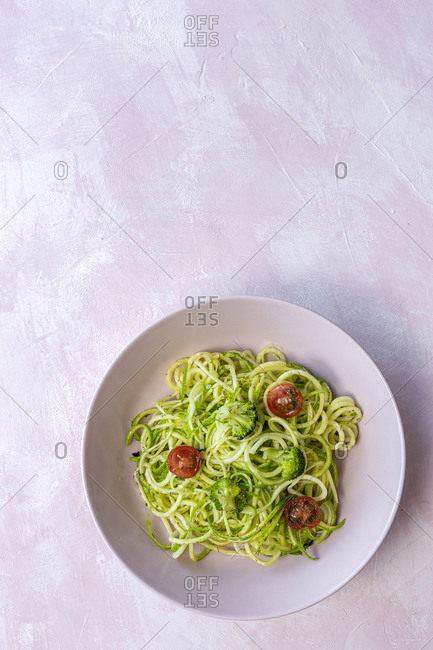 Homemade Zucchini Spaghetti with pesto sauce, broccoli and cherry tomatoes from above. Vegan food concept. Flat lay. Top view