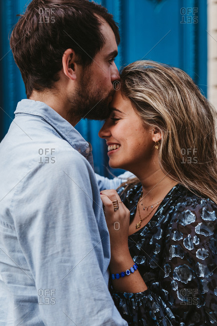 Side view of happy young couple in casual clothes hugging and kissing while standing against aged stone building with blue doors on city street