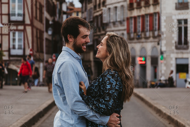 Side view of cheerful young couple in casual wear embracing and looking at each other with love while standing on street against old building during romantic holidays in France