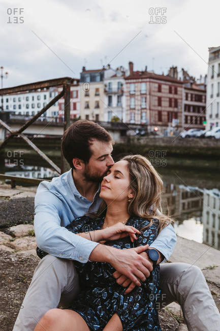 Positive young couple in casual clothes enjoying romantic date while sitting together on stone border in city with old buildings in background