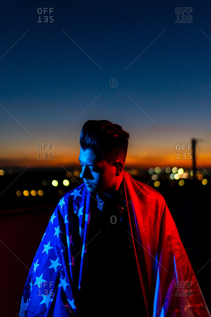 Serious young male in black leather jacket with American flag resting on shoulders looking at camera while standing in red and blue lights on dark street against sunset evening sky