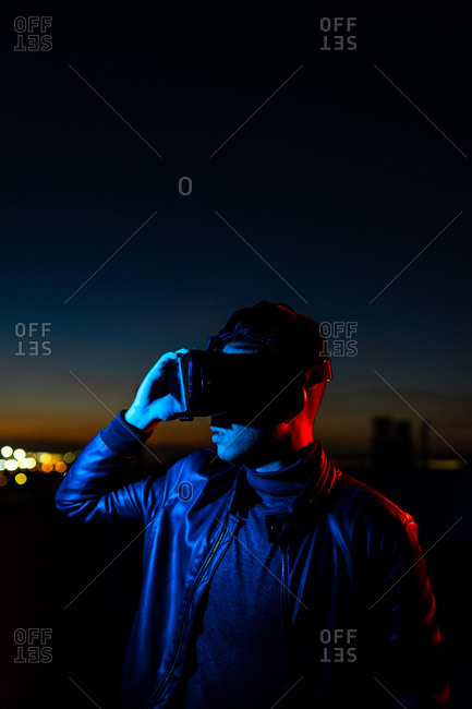 Modern male with VR headset exploring virtual world while standing in red neon light on street against dark sunset sky