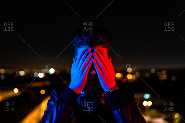 Contemporary young guy covering face with hand while standing under bright red and blue light on blurred background of city street at night