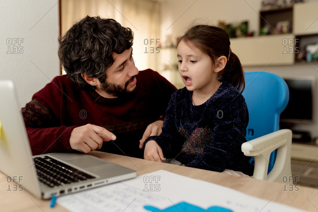 Bearded adult man sitting near little girl with laptop and helping daughter with remote education while staying at home together