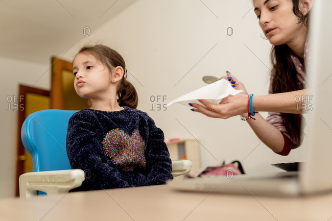 Crop adult woman trying to give food to naughty little girl using laptop for studies at home