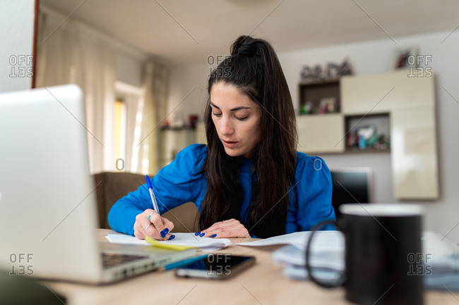 Focused woman making notes while sitting at table with laptop and papers and doing remote job in cozy room at home