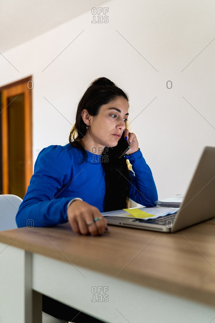 Brunette woman answering a phone call sitting at table with laptop and working on remote project at home