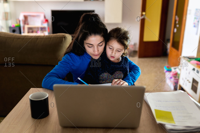 Busy woman hugging little girl and reading papers while sitting at table with laptop and working on freelance project at home