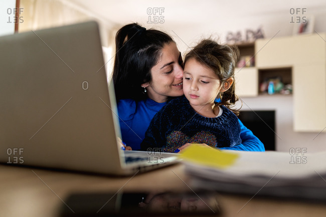 Adult woman hugging and kissing little girl using laptop to trying to do freelance project while playing with daughter and working at home
