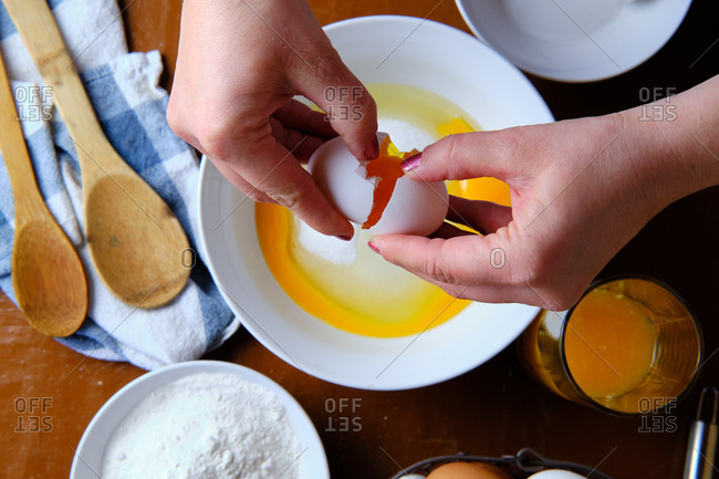 Unrecognizable woman breaking raw chicken egg over bowl with sugar near wheat flour during pastry preparation at home