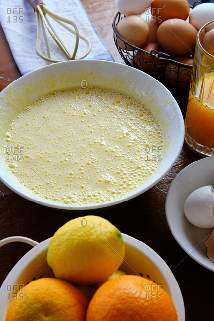 Mixed liquid pastry batter near eggs and citrus juice on kitchen table