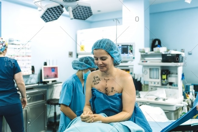 Adult woman with marks on breast and chest sitting on operating table near surgical team before plastic surgery in modern clinic