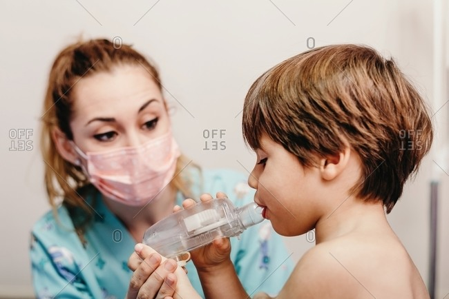 Little kid using inhaler in clinic during check up