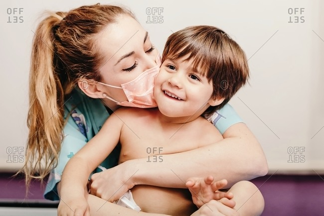 Cheerful young female in protective medical mask hugging and kissing cute laughing little patient