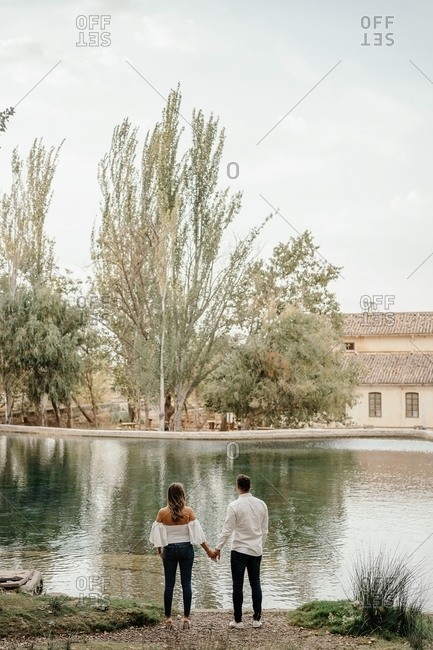 Back view of unrecognizable man and woman holding hands while standing on shore of calm pond during romantic date in garden