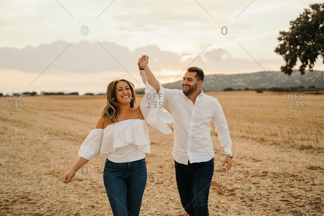 Full body cheerful man and woman holding hands and running on dry field grass during romantic date in evening in countryside