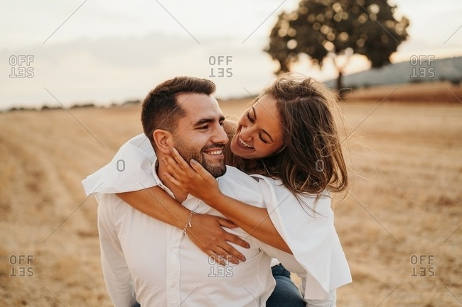 Cheerful man giving piggyback ride to excited girlfriend during romantic date in dry meadow in evening