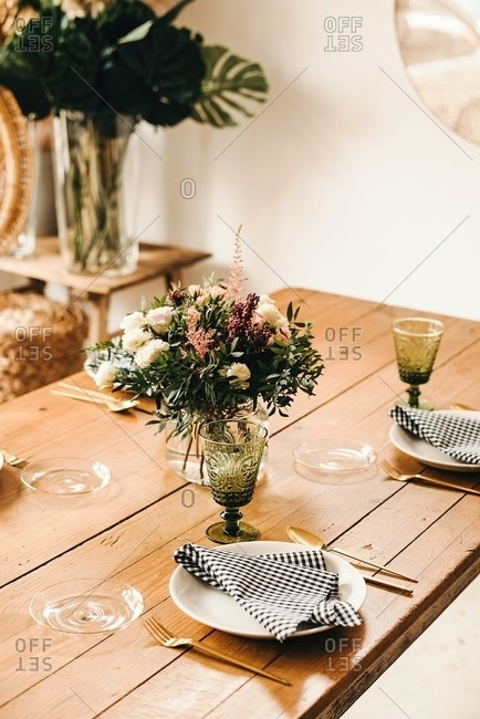 Bouquet of miscellaneous flowers and green plant twigs in vase with water on a wooden table set for a meal