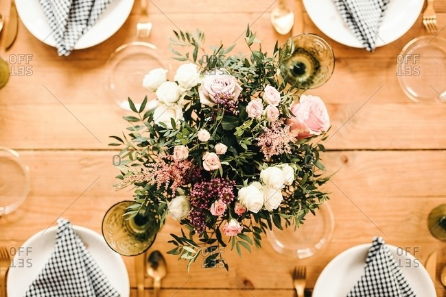 From above top view bouquet of miscellaneous flowers and green plant twigs in vase with water on a wooden table set for a meal