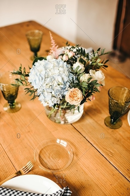 From above bouquet of miscellaneous flowers and green plant twigs in vase with water on a wooden table set for a meal