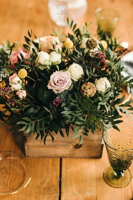 From above bouquet of miscellaneous flowers and green plant twigs in a wooden box on a timber table set for a meal