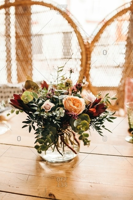 Bouquet of miscellaneous flowers and green plant twigs in vase with water on a wooden table set for a meal with beautiful designed rattan chair on the background