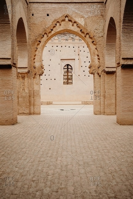 Aged stone building with columns and ornamental carved arches in old city Marrakesh in Morocco