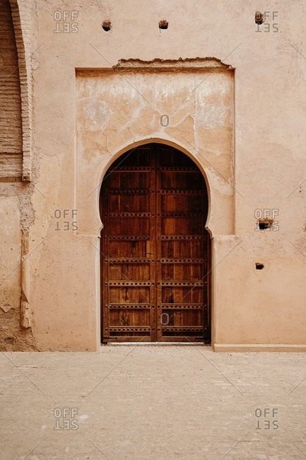 Exterior of aged stone building in traditional Arabic style with ornamental arched door in Morocco