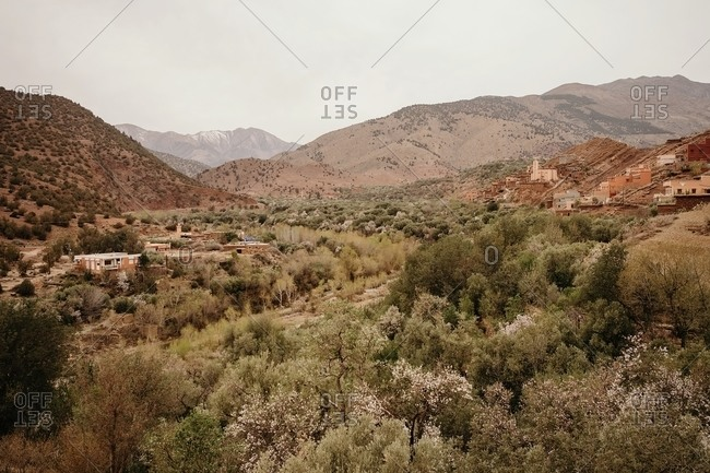 Moroccan landscape with small stone houses located among hills with green vegetation on mountainous terrain