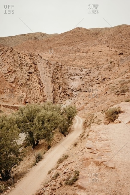 Empty curved dirt road going through dry desert valley among mountains in Moroccan countryside