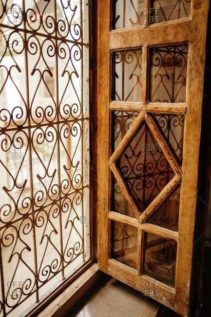 Old vintage window with wooden frames and ornamental grid in ancient house in Marrakesh city