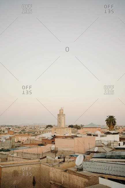 Marrakesh, Morocco - February 18, 2020: Amazing aerial view of ancient cityscape with stone houses and green potted plants placed on roofs under clear morning sky