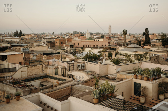 From above aerial view amazing cityscape of ancient Marrakesh city with stone houses and green potted plants placed on roofs under clear morning sky