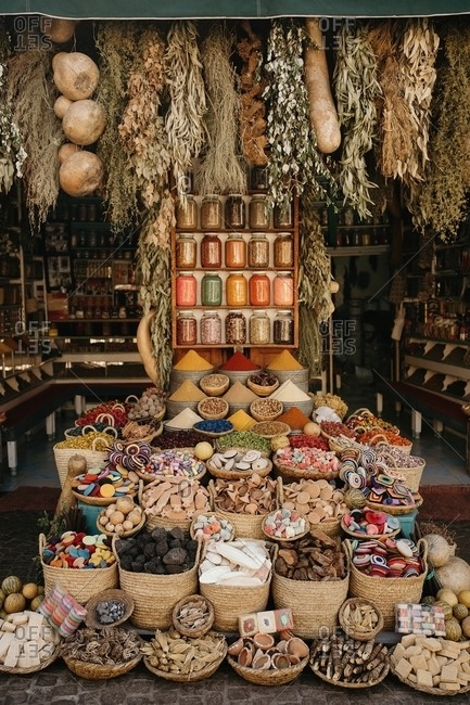 Various colorful spices and dry herbs with assorted typical products for sale in small local shop in Marrakesh in Morocco