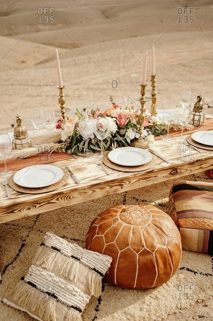 From above of long wooden table decorated with flowers and candles and served with white plates placed on carpet near traditional Arabic seats with sandy dunes in background