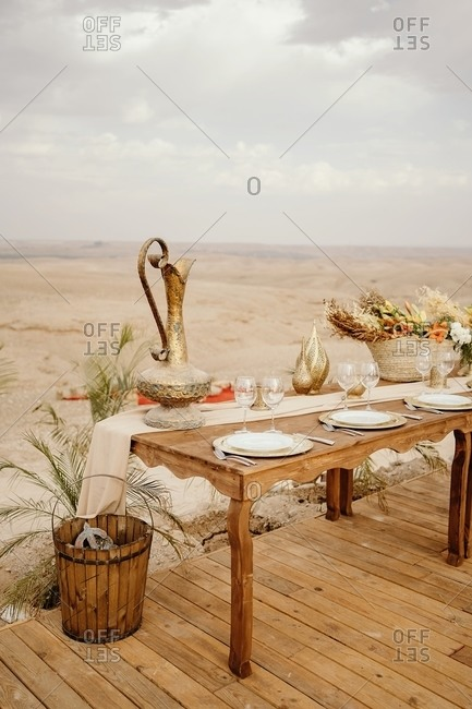 Long wooden table decorated with flowers and candles and served with white plates on traditional Arabic set with sandy dunes in background