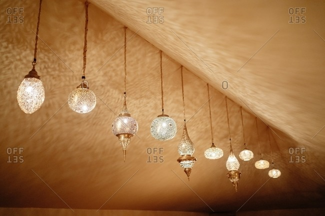 From below of various bright glowing lanterns in traditional Moroccan style hanging under ceiling in room