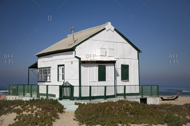 Small white country house with green fence located at seaside against cloudless blue sky in sunny day