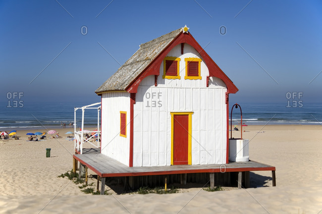 Small white country house with red door and windows located at seaside against cloudless blue sky in sunny day