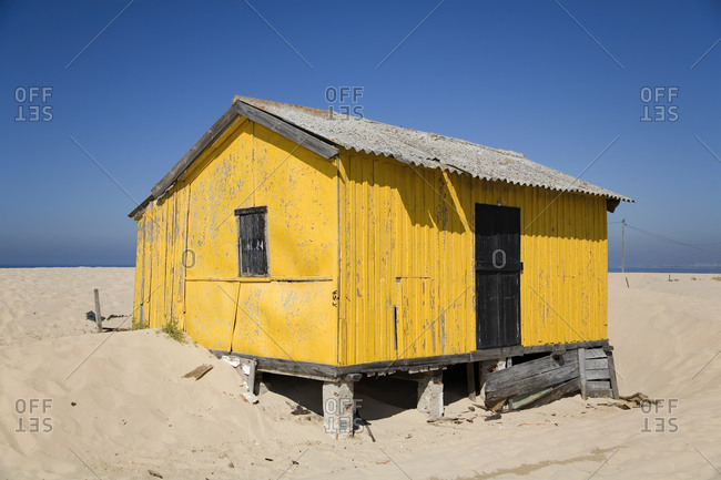 Small colorful house with shabby walls located on sandy seaside with blue sky in background in sunny day