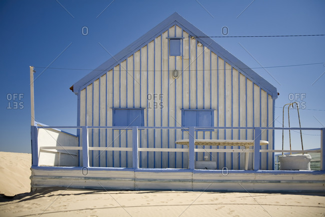 Small white and blue strips country house with white fence located at seaside against cloudless blue sky in sunny day