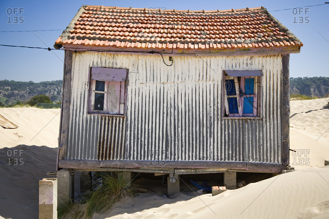 Small house with shabby walls located on sandy seaside with blue sky in background in sunny day