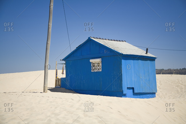 Small blue house with shabby walls located on sandy seaside with blue sky in background in sunny day