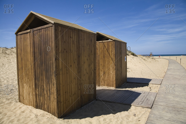 Small plank wooden booths and pathway on sandy seashore in sunny day with blue sky in background