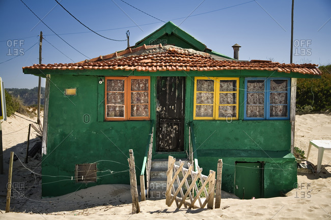 Small house with shabby green walls and colorful windows located on sandy seaside with blue sky in background in sunny day