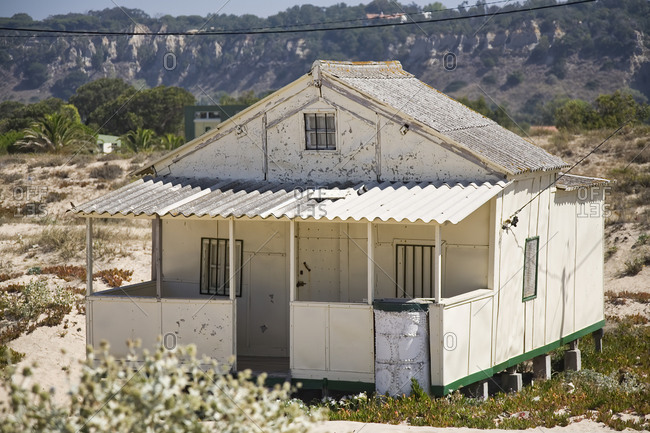 Exterior of small residential house with shabby white walls built on stilts on hilly terrain in sunny day in countryside