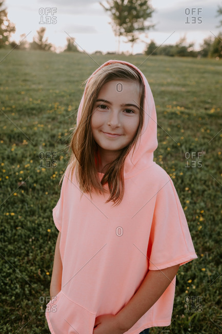 Adorable little girl standing in a park looking at camera