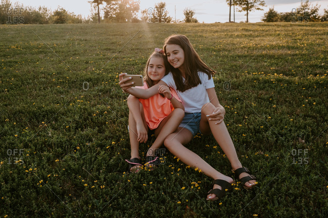 Adorable sisters sitting in a park and taking a selfie